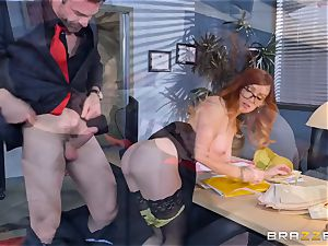 Dani Jensen toying with pink cigar in the office
