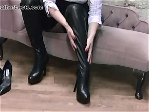 handsome secretary leisurely pulls on her leather thigh boots
